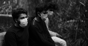 Men sat on a bench with masks on