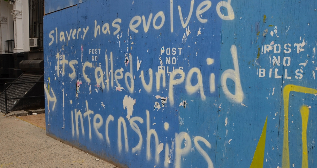 Graffiti saying 'Slavery has evolved it's called unpaid internships'